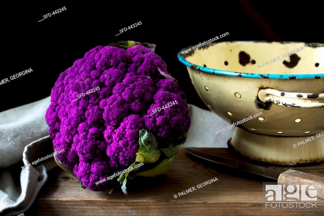 Stock Photo: Purple cauliflower on wooden table.