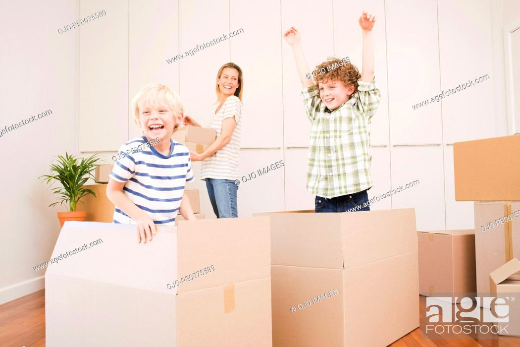 Stock Photo: Mother and children unpacking boxes in new house.