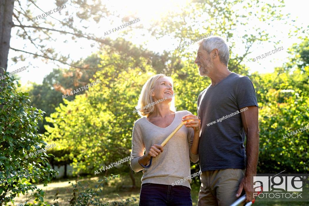 Photo de stock: Smiling mature couple with gardening equipment standing in backyard.
