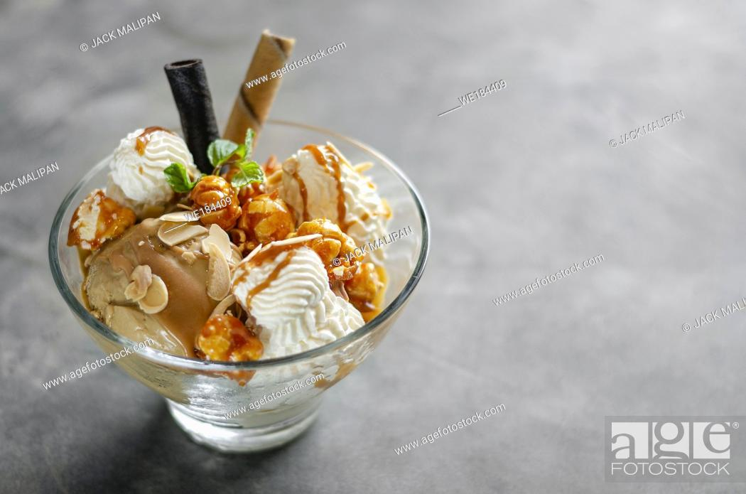 Imagen: caramel and almond ice cream with caramelized popcorn sundae dessert in glass bowl.