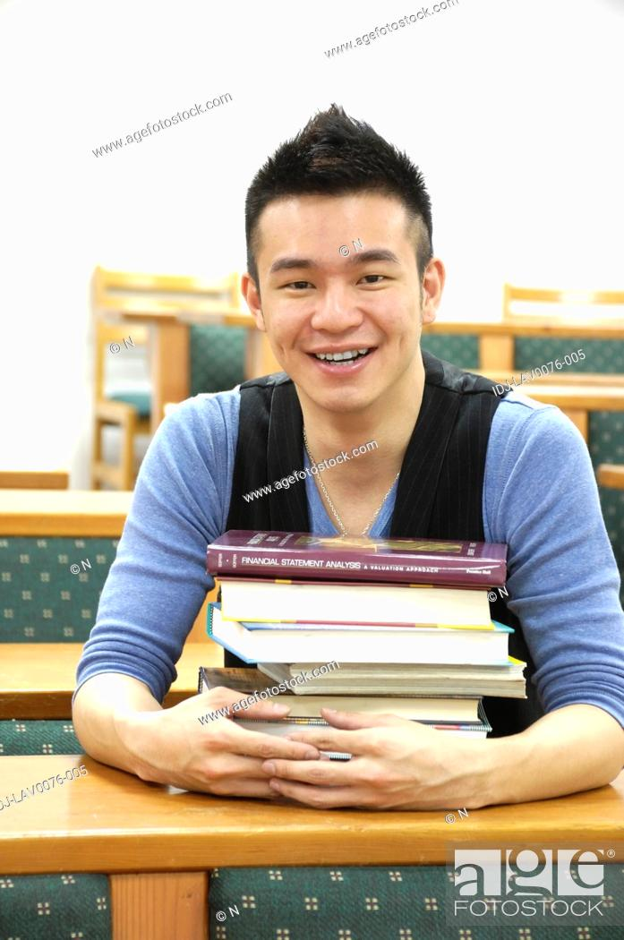 Stock Photo: Male university student sitting with a stack of books in a classroom.