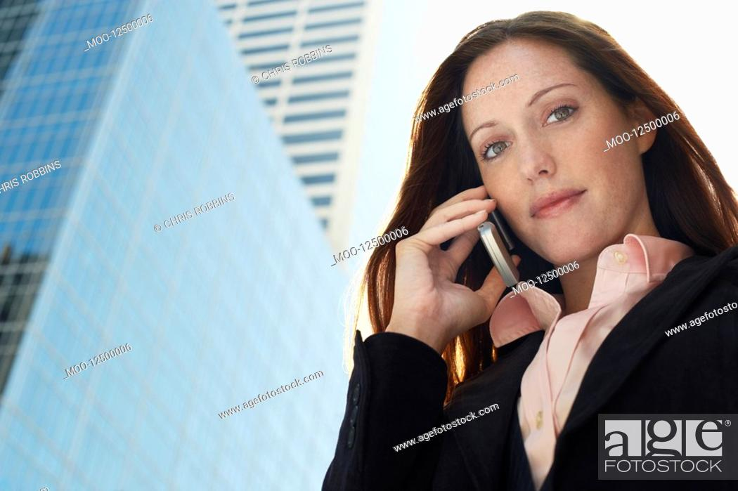 Stock Photo: Young woman using mobile phone outdoors portrait.