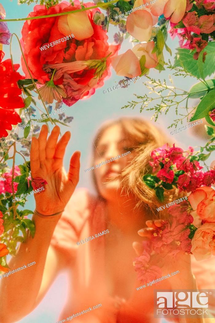 Stock Photo: Beautiful woman behind glass ane touching flowers.