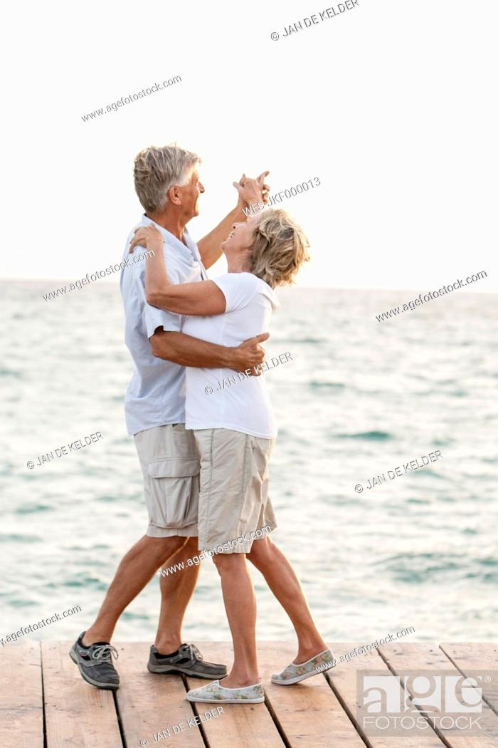Stock Photo: Spain, Senior couple dancing on jetty at the sea.