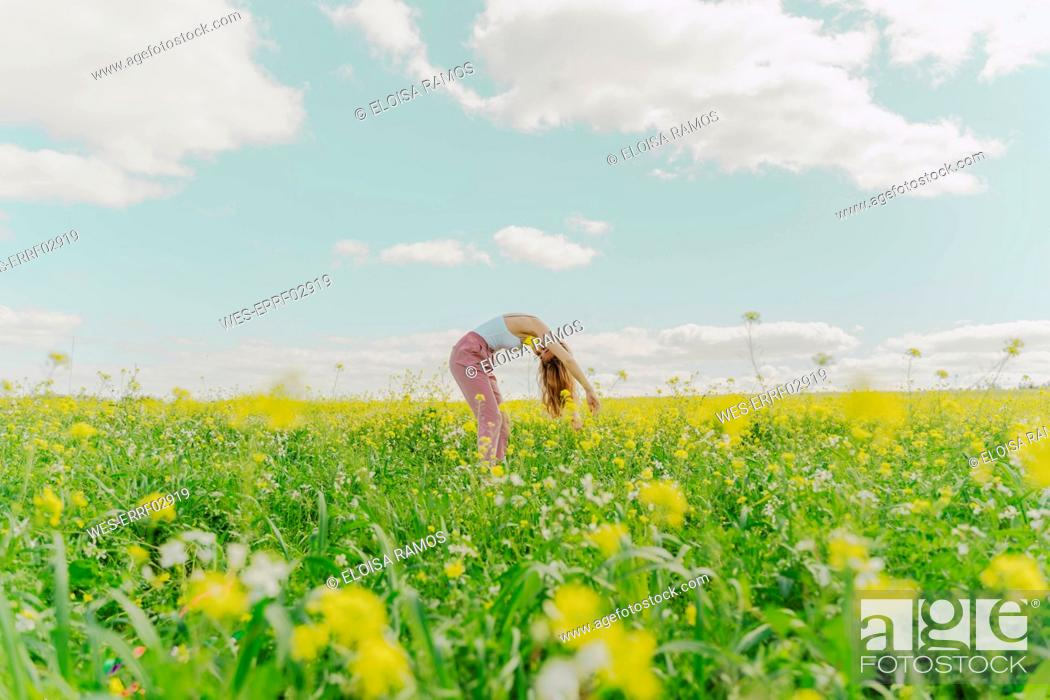 Stock Photo: Young woman bending over in a flower meadow in spring.