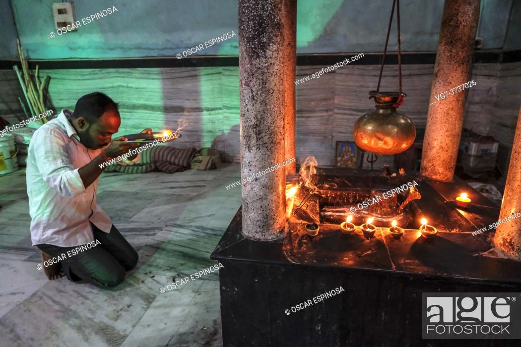 Stock Photo: Tezpur, India - November 2020: A man making an offering to celebrate Diwali at the Ganesh Ghat temple on November 14, 2020 in Tezpur, Assam, India.
