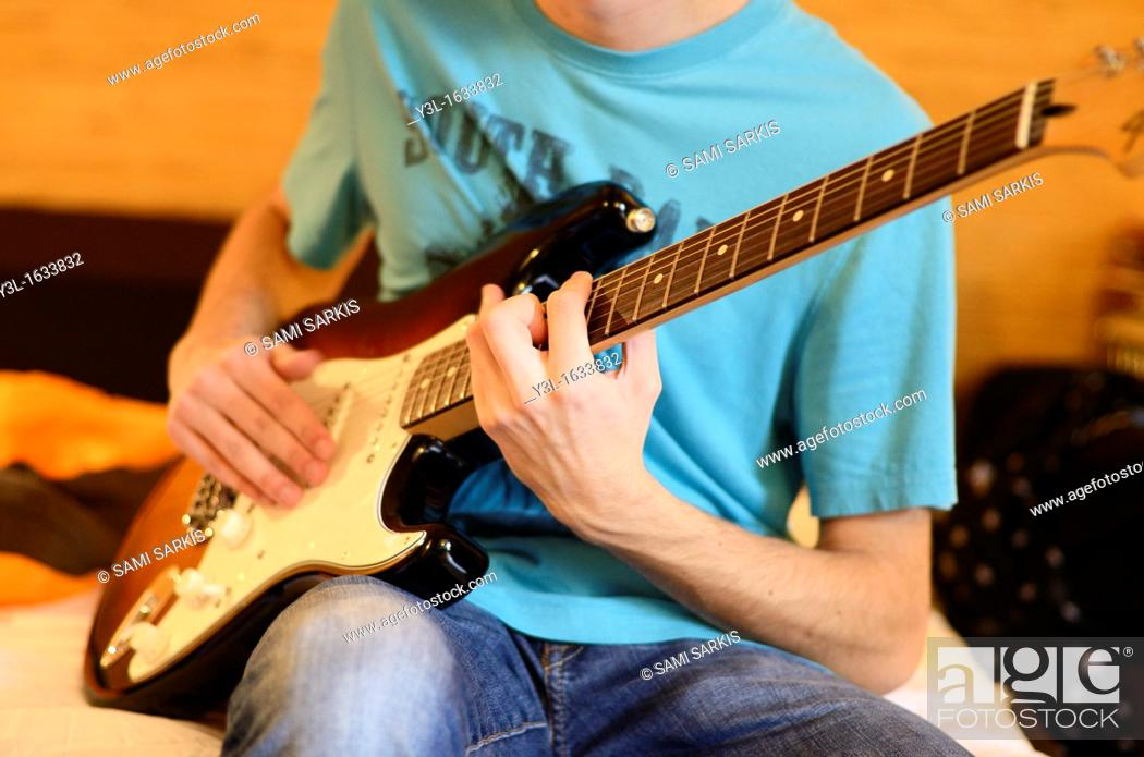Teenage Boy Playing Electric Guitar On Bed Stock Photo Picture And