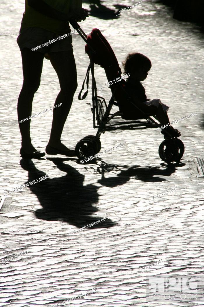 Stock Photo: mother pushing pram buggy in street.
