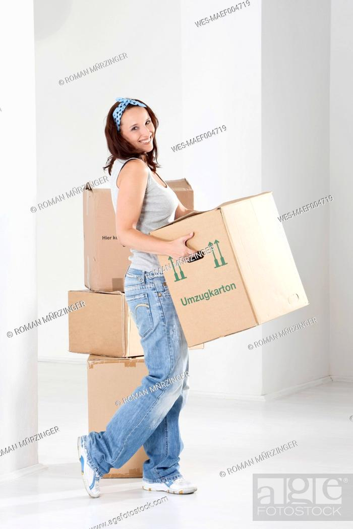 Stock Photo: Young woman carrying cardboard box, smiling, portrait.