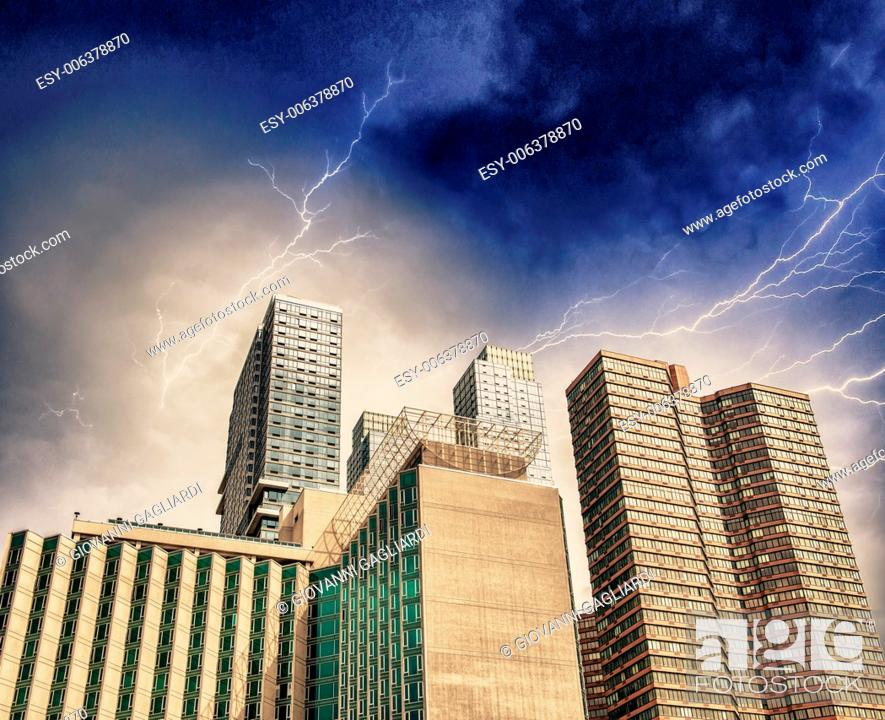 Stock Photo: Storm over New York Skyline. Manhattan skyscrapers with dramatic sky.