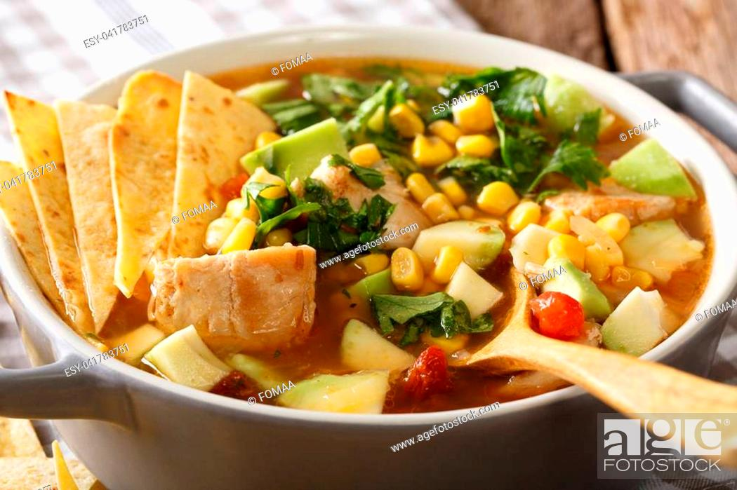 Stock Photo: Delicious tortilla soup with chicken, greens, tomatoes, avocado and corn close-up in a saucepan. horizontal.