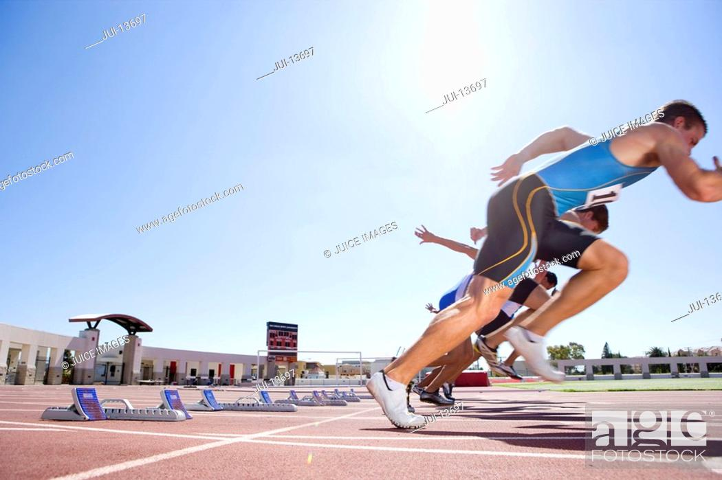 Stock Photo: Male sprinters leaving starting blocks, low angle view sun flare.