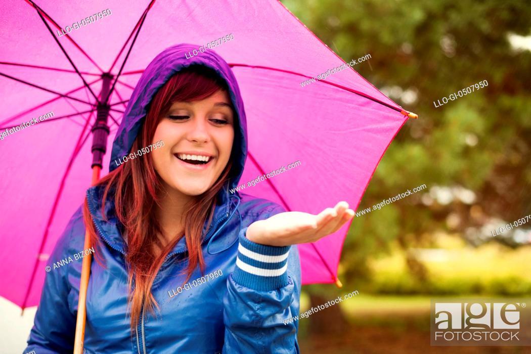 Stock Photo: Cheerful woman under pink umbrella checking for rain, Debica, Poland.