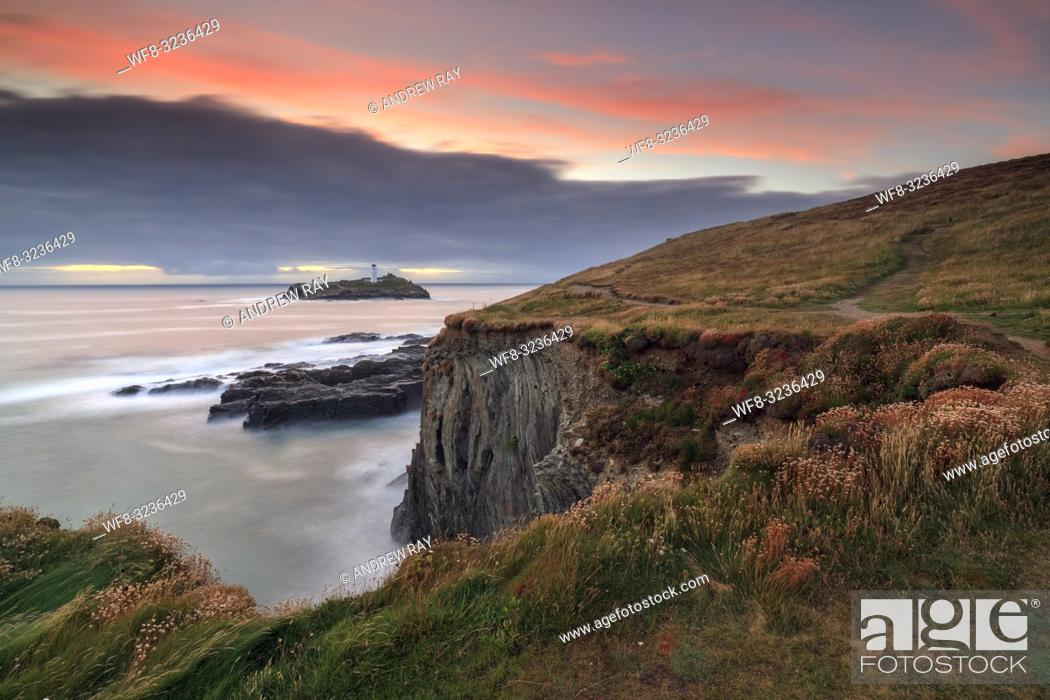 Stock Photo: The lighthouse on Godrevy Island in Cornwall captured using a long exposure to blur the movement in the water. The image was taken at sunset from near Godrevy.