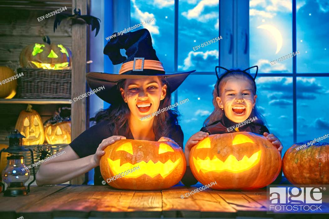 Stock Photo: Mother and her daughter having fun at home. Happy Family celebrating for Halloween.