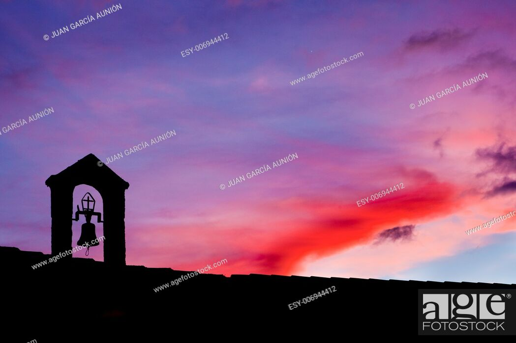 Stock Photo: silhouette of Old belfry lighted with the last ray of light at sunset , Montanchez, Spain.