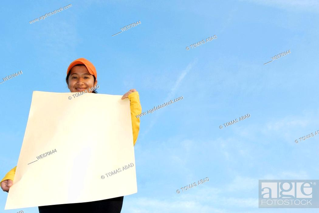 Imagen: Woman holding a blank poster - advertisement sign.