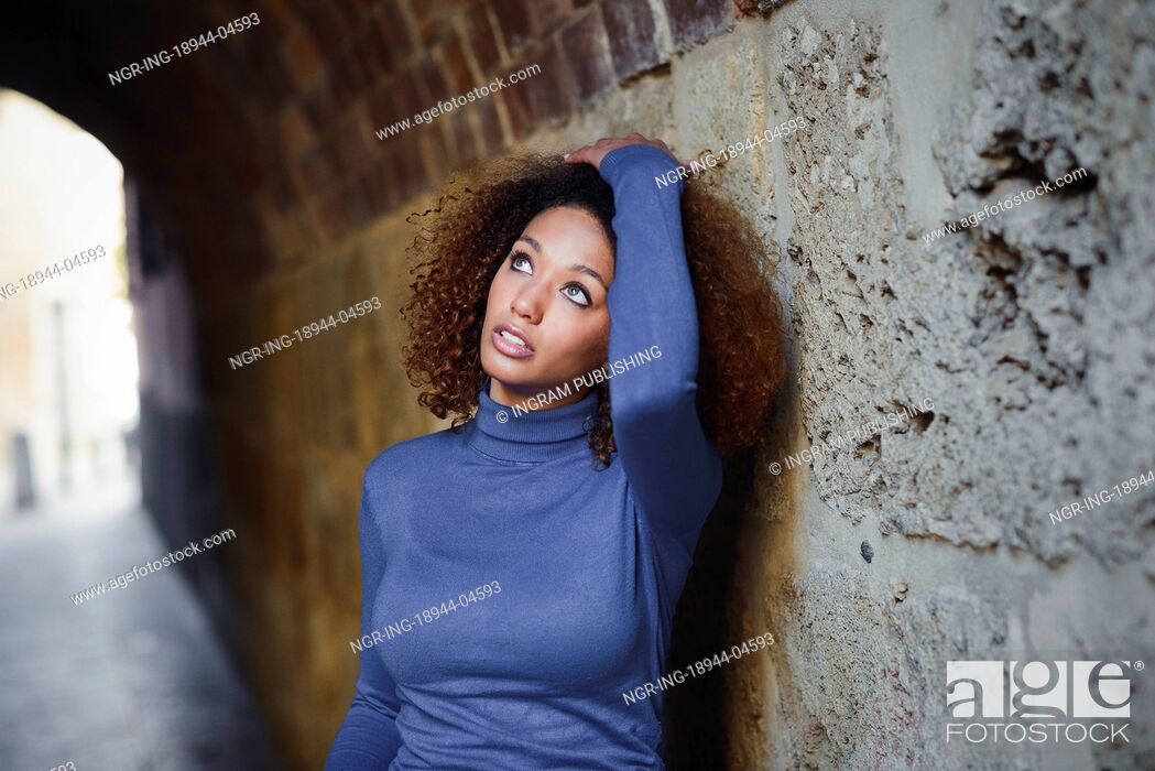 Stock Photo: Beautiful young African American woman, model of fashion, with afro hairstyle and green eyes wearing blue sweater in urban background.