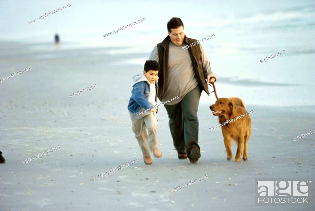 Stock Photo: Father and son walking on the beach.