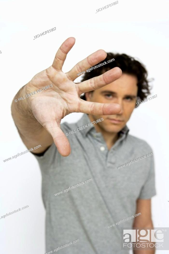 Stock Photo: Young man holding up his hand.