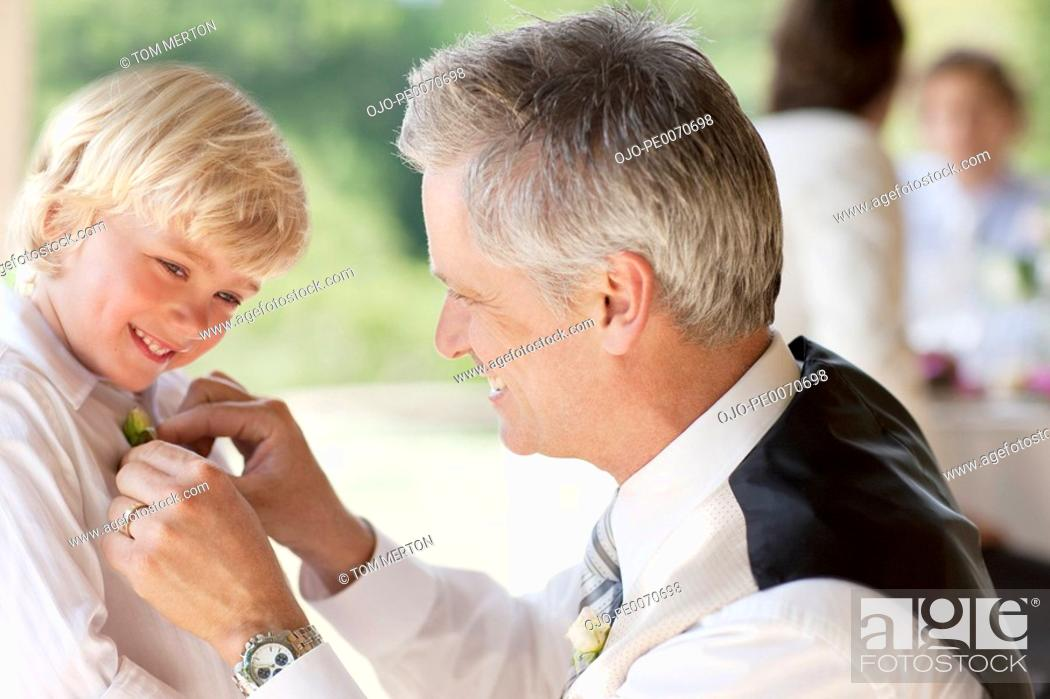 Stock Photo: Father adjusting son's tie at party.