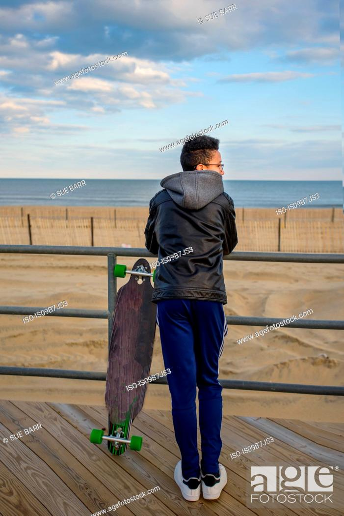 Photo de stock: Young boy leaning against railings, looking at view, skateboard beside him, Asbury, New Jersey, USA.