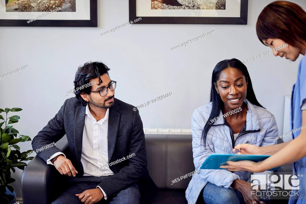 Stock Photo: Receptionist talking to patient in waiting room of a dental practice.