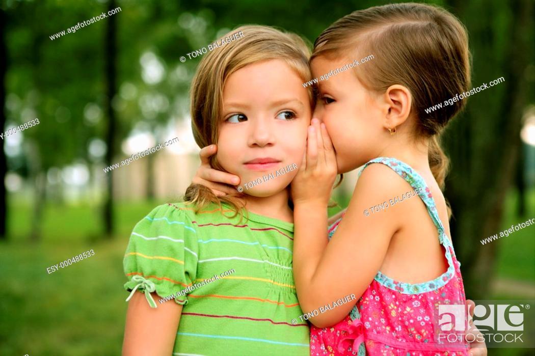 Photo de stock: Two twin little sister girls whisper in the ear, outdoor on green park.