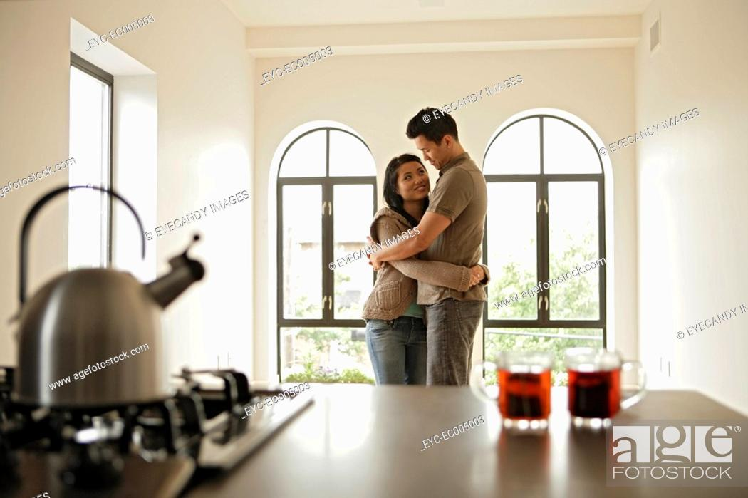 Stock Photo: Two people embracing, side view.