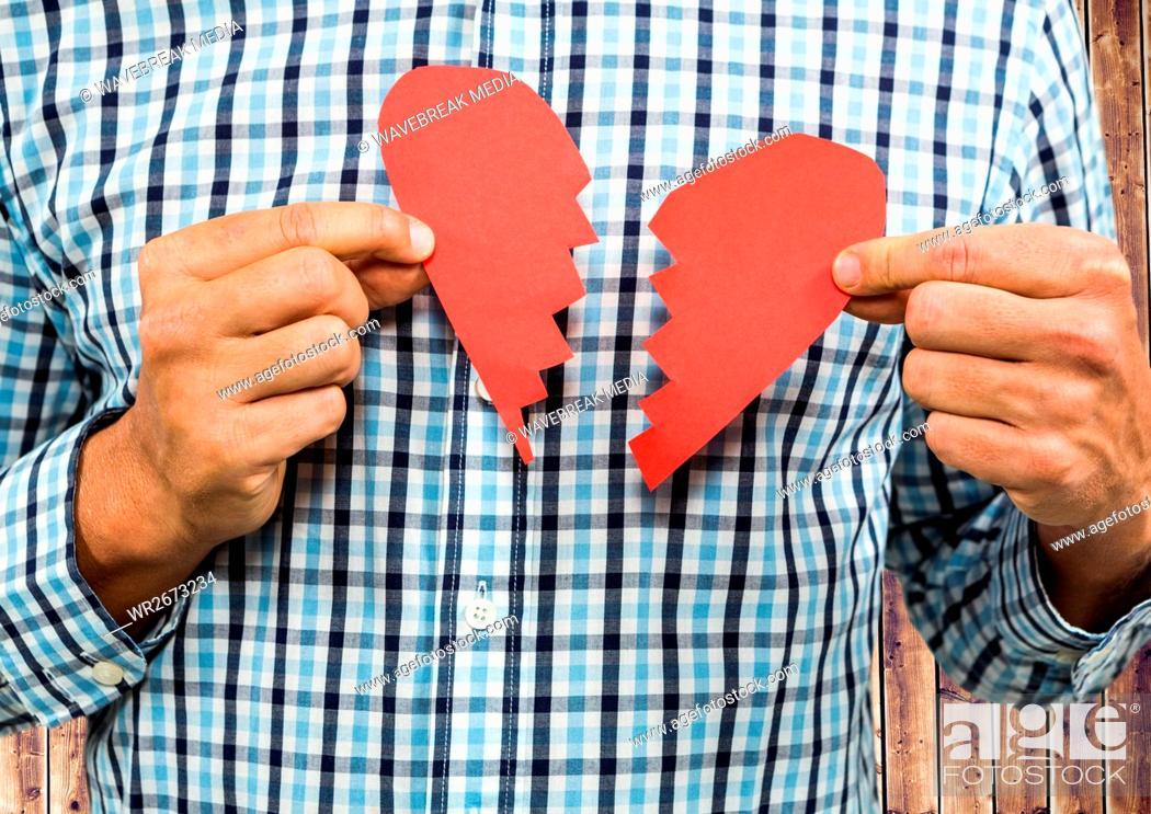 Stock Photo: Man holding broken heart.