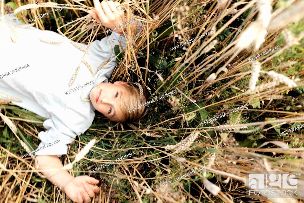 Imagen: Portrait of blond boy with oat ear in mouth lying in an oat field.