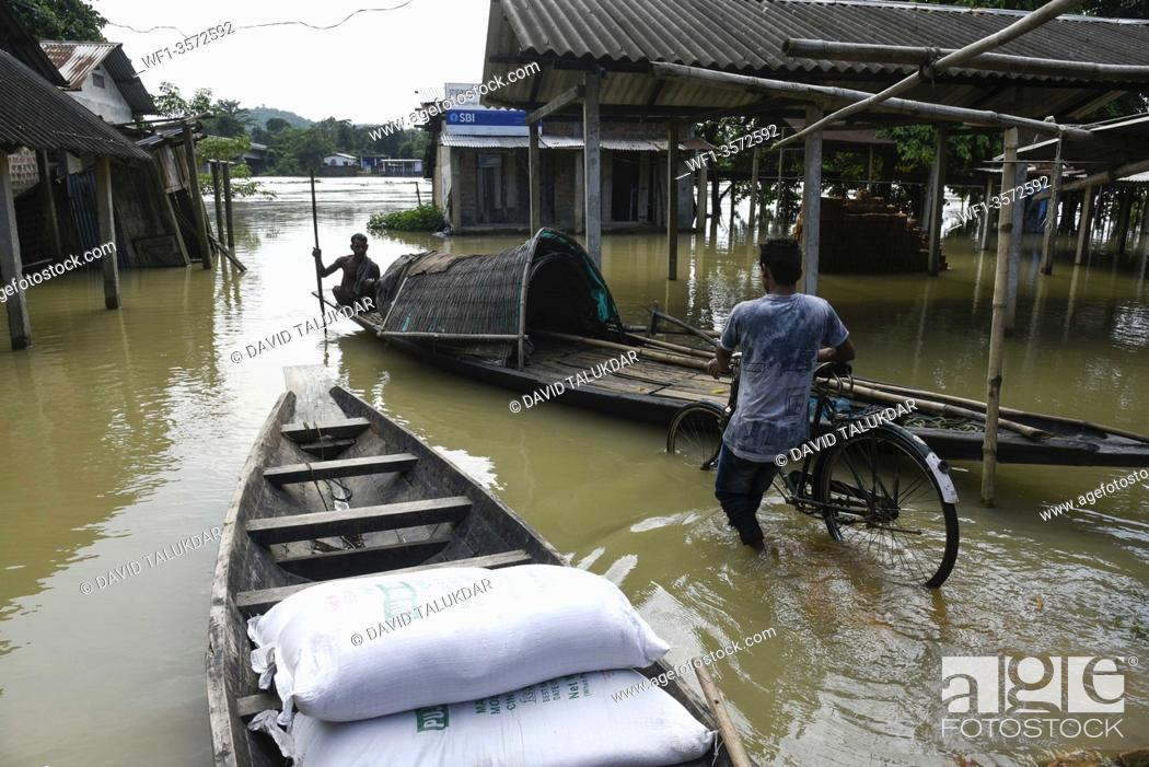 Stock Photo: Villager uses a country boat to move across a flooded locality in Morigaon district of Assam, Monday, July 13, 2020.