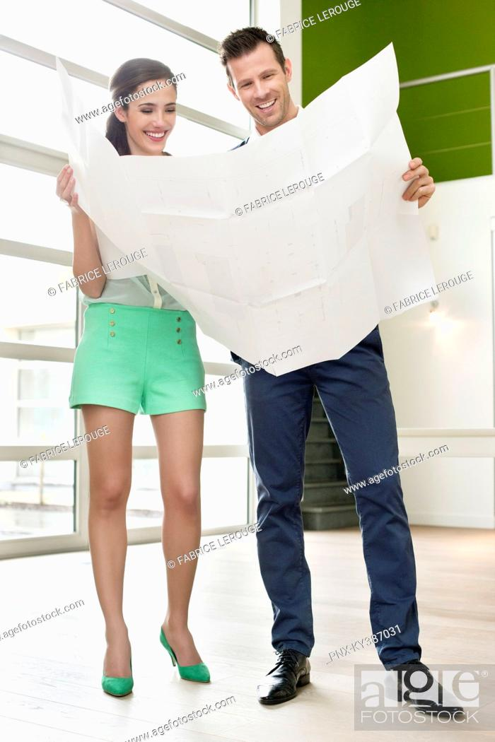 Stock Photo: Couple reading a blueprint at their new home.