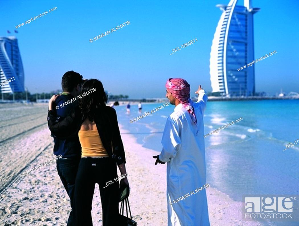Stock Photo: Arab man shows western tourists the Burj Al Arab hotel in Dubai, UAE.