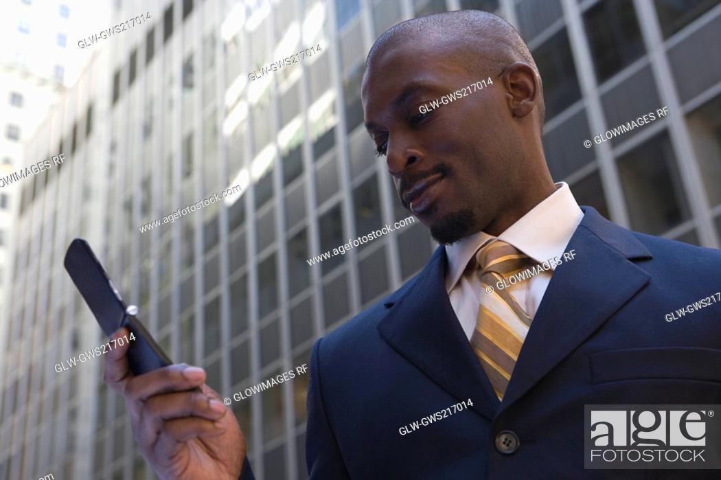 Stock Photo: Low angle view of a businessman using a mobile phone.