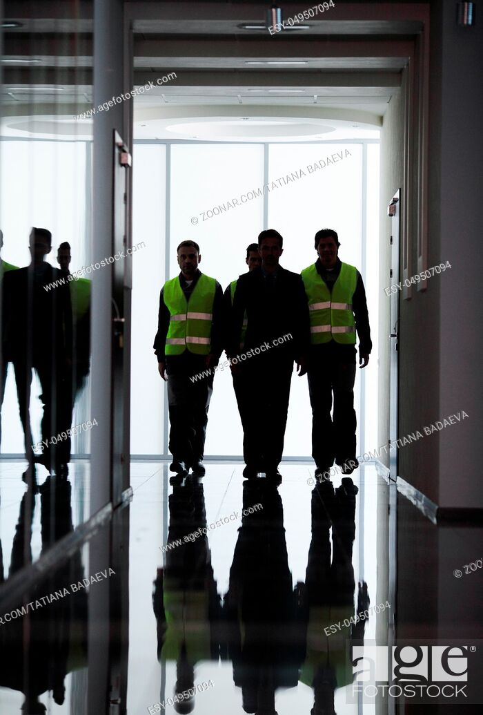 Stock Photo: Team of workers and manager walking at the corridor of factory.