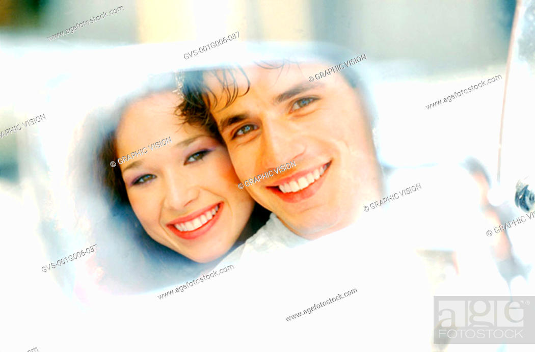 Stock Photo: Reflection of a couple smiling in a rear view mirror.