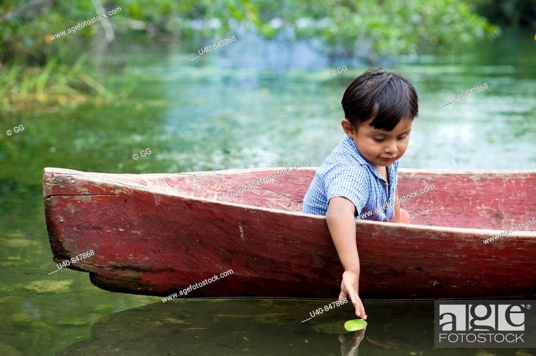 Stock Photo: Guatemala, Rio Dulce, young boy in canoe.
