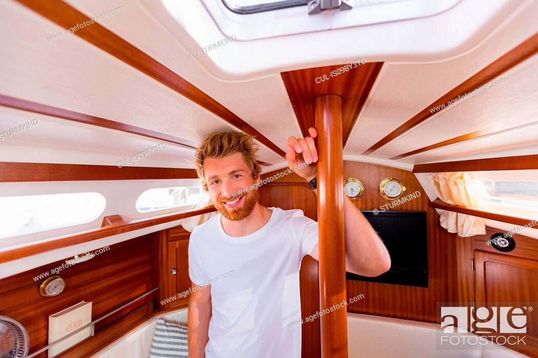 Stock Photo: Young man in sailboat cabin, portrait.