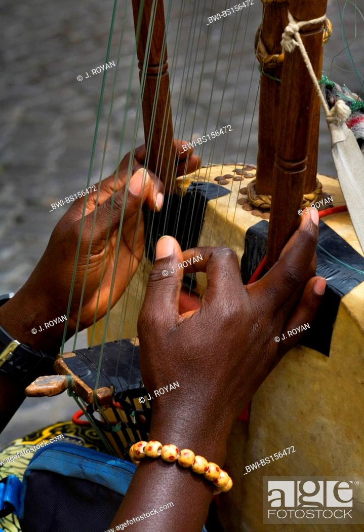 Black hands playing the strings of a 21 string Kora harp