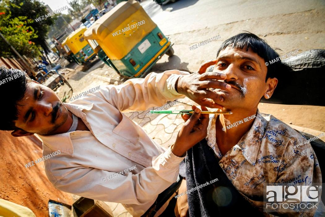 Stock Photo: India, Ahmedabad, Street barber shaving customer.