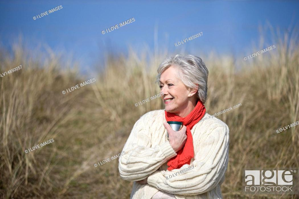 Stock Photo: A senior woman sitting amongst the sand dunes, holding a hot drink.