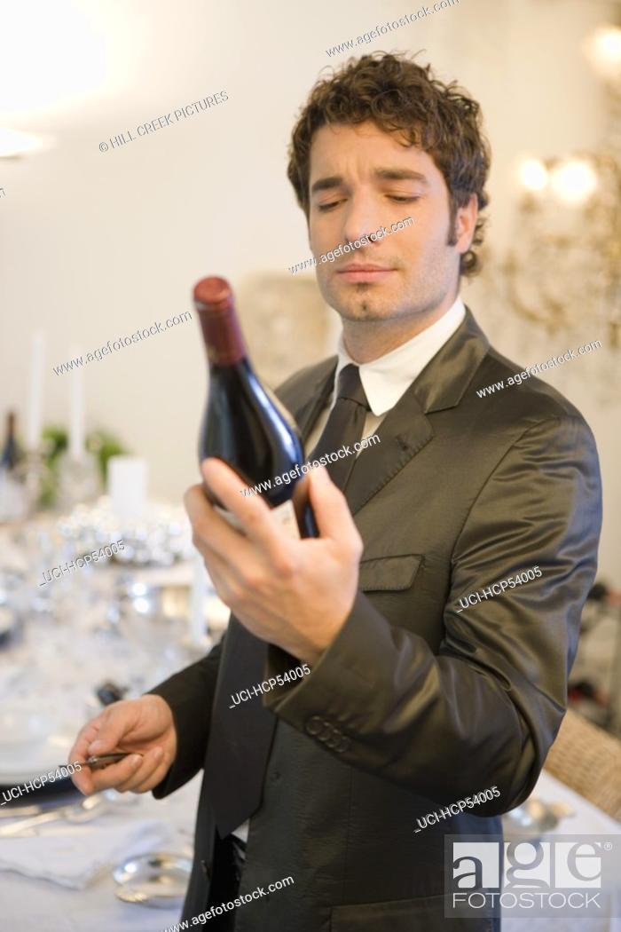 Stock Photo: Man examining bottle of wine.