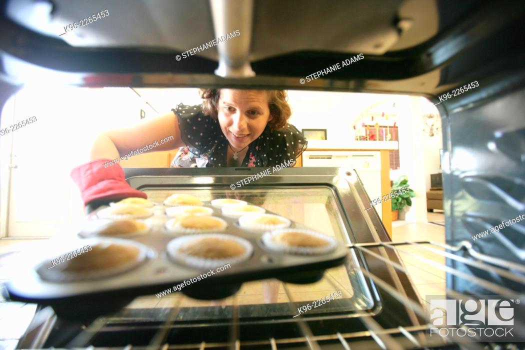 Stock Photo: Looking out from inside the oven as a woman pulls out freshly baked cupcakes.