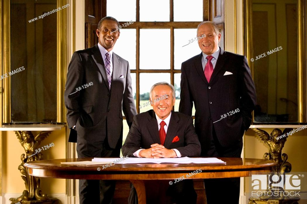 Stock Photo: Mature businessman at desk flanked by colleagues, smiling, portrait.