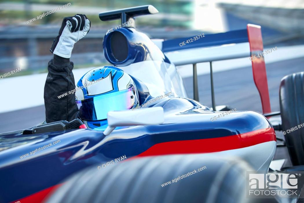 Imagen: Portrait formula one race car driver wearing helmet and cheering with fist on sports track.