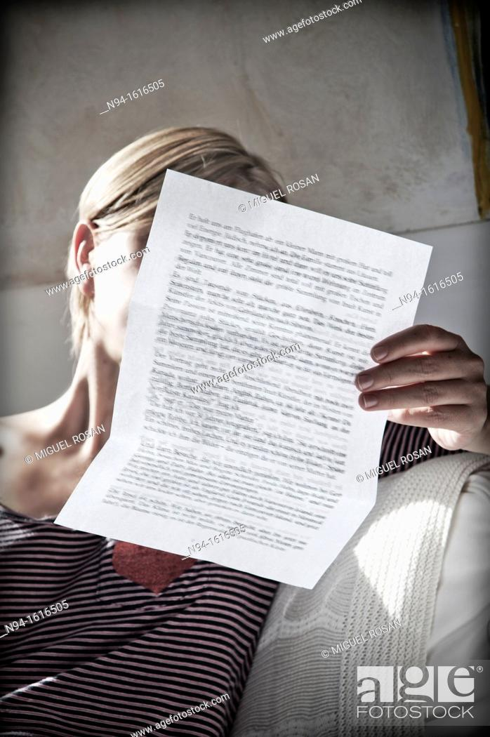 Stock Photo: Young woman relaxing, reading a personal letter to the sunlight coming through the bedroom window.