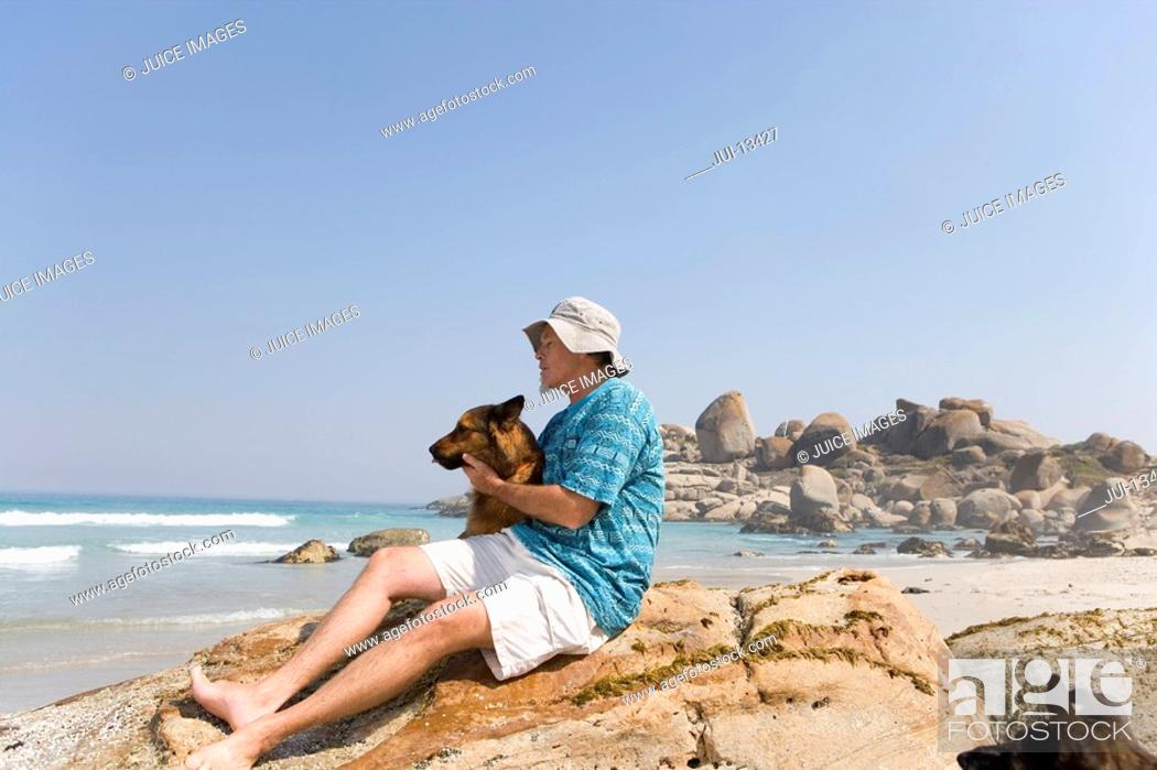 Stock Photo: Man embracing dog on rock on beach, low angle view.