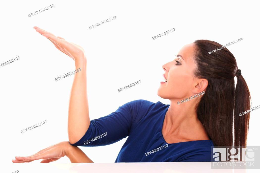 Stock Photo: Pretty woman in blue shirt holding palm up while looking to her right in white background - copyspace.