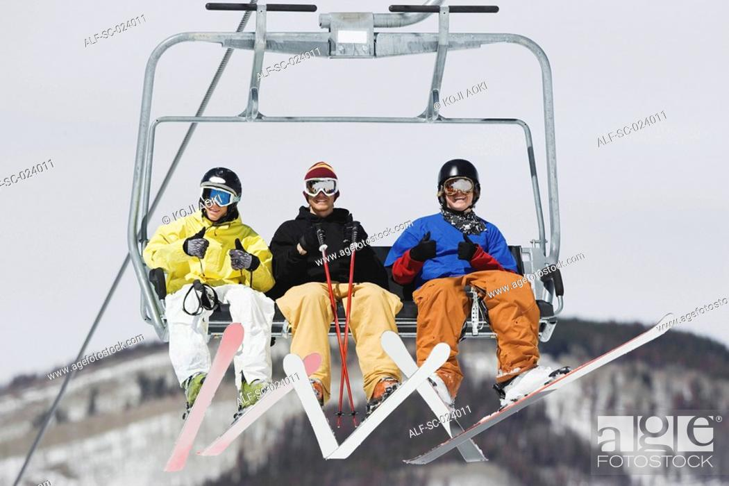 Stock Photo: Three Skiers in a Lift.